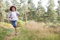 Boy Running Through Woods Stock Image