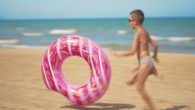 The boy runs along the beach with a pink inflatable donut, rolls it along the sand against the background of the sea. The concept of relaxation and fun stock video footage