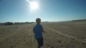 Boy runs along the seashore stock video