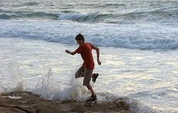 Boy runs along the shore. Of the Mediterranean Sea in Israel Stock Photography
