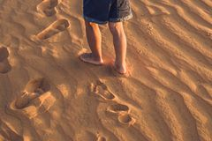 The boy runs around the red desert at dawn. Traveling in a fuss. With children concept Royalty Free Stock Photography
