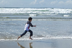 Boy runs on beach. Royalty Free Stock Photos