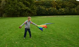 The boy runs a kite. The boy runs a bright kite on a green meadow Royalty Free Stock Images