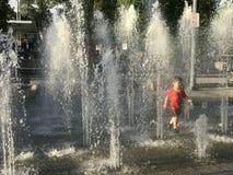 Boy runs through fountain Stock Photos