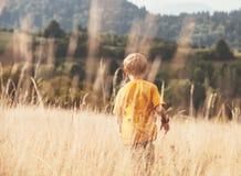 Boy runs in high yellow grass Stock Photography