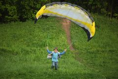 Boy runs from hill with parachute Stock Photos