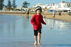 A boy runs on the ocean shore in Morocco stock image