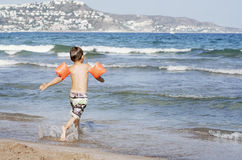 The boy runs to the sea with armbands for swimming. Stock Photography