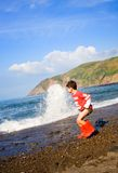 Boy runs from waves Stock Photos