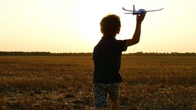 The boy runs through the wheat field after the harvest. The child holds a toy plane in his hand and imagines flying