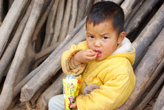 Boy in rural China. Teng country Guangxi, China - January 2, 2011: a boy sit on the countryside roadside eating food Stock Photos