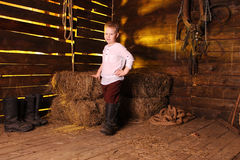 Boy in a rural clothes and canvas boots. Child in a white shirt, trousers and boots at the background of haystacks Stock Images
