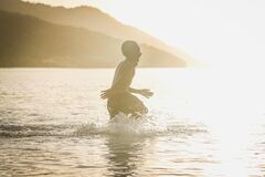 Boy Rushing Into the Body of Water during Daytime Royalty Free Stock Photography