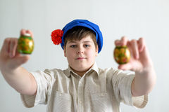 Boy in Russian national cap with cloves holding easter eggs Royalty Free Stock Photography