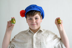 Boy in Russian national cap with cloves holding easter eggs Stock Photo