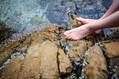 Boy's bare feet on the rock. Teenaged boy sitting on a rock with wet bare feet Stock Images