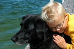 Boy's Best Friend. A boy hugs his pet black labrador retriever on the dock of a Minnesota lake Stock Image