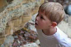 Boy's expression of amazement. Five-year old blond-haired boy looks at something in amazement and wonder, very curious and interested in a sea wall with Royalty Free Stock Photo