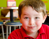 Boy's face covered with chocolate from yogurt Royalty Free Stock Image