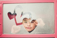 Boy's face in a heart frame. A little boy behind a glass with a heart frame Royalty Free Stock Photo
