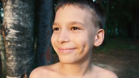 A boy is happily looking and smiling at sunset among trees near parent's summer house stock video footage