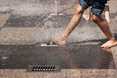 Boy's feet in blue jeans playing in the fountain Royalty Free Stock Photos