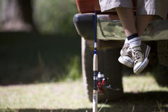 Boy?s feet next to fishing pole Royalty Free Stock Images