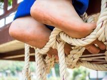 Boy`s feet step on a rope Stock Photos