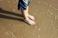 Boy's feet on a wet sand. A boy standing on a shore with barefoot, enjoing the feeling of wet sand royalty free stock photo
