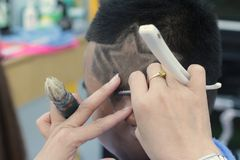 The boy's haircut with clipper and razor in the barber shop.  stock images