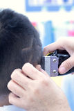 The boy's haircut with clipper and razor in the barber shop Stock Photo