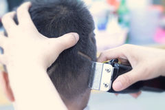 The boy's haircut with clipper and razor in the barber shop Stock Photos