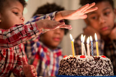 Boy's hand over cake's candle. Stock Photos