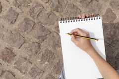 Boy`s hand with a pencil over an open notepad in the park stock image