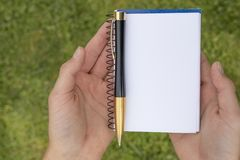 Boy`s hand with a pencil over an open notepad in the park stock photo