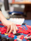 Boy's hand picking plastic toys. Boy's hand picking some plastic pieces for building a toy Stock Image