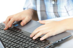 Boy's hand typing on laptop keyboard Stock Photos
