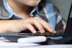Boy's hand typing on laptop keyboard Stock Image
