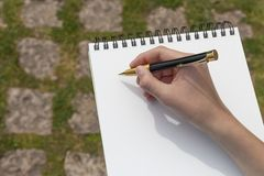 Boy`s hand with a pencil over an open notepad in the park royalty free stock image