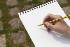Boy`s hand with a pencil over an open notepad in the park royalty free stock photos