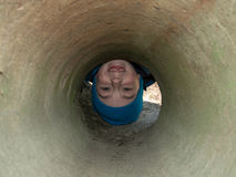 The boy's head in the concrete pipe Royalty Free Stock Image