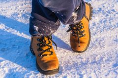 The boy`s legs in boots standing on snow royalty free stock images