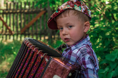 The boy's portrait in a plaid shirt with an accordion in a garden Stock Photo