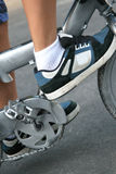 Boy's sneakers and bicycle pedals. Close up of boy ready to peddle a bicycle Stock Photos