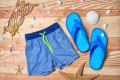 Boy`s swimming trunks and flip flops on wooden background. Boy's swimming trunks and flip flops on wooden background Stock Image