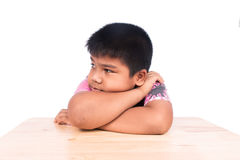 Boy sad siting alone at wooden table. Little boy sad siting alone at wooden table royalty free stock photos