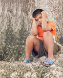 boy sad sitting alone under big tree Stock Photography