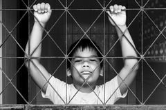 Boy sad standing alone behind jail Royalty Free Stock Photography