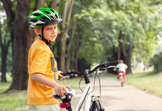 Boy in safe helmet with bicycle in city park Stock Image
