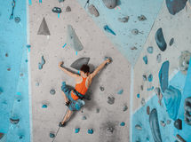 Boy in safety equipment climbing in gym Royalty Free Stock Photos